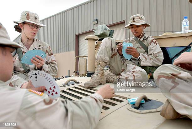 US soldiers guarding the Media Center at Camp Al Saliya in Doha Qatar play cards March 19 2003 on the hood of a truck to kill time The camp is the...