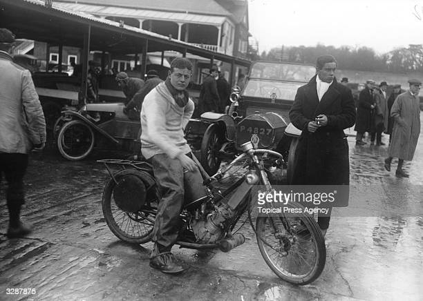 People milling around with motor cycles at Brooklands when a university meeting is rained off.