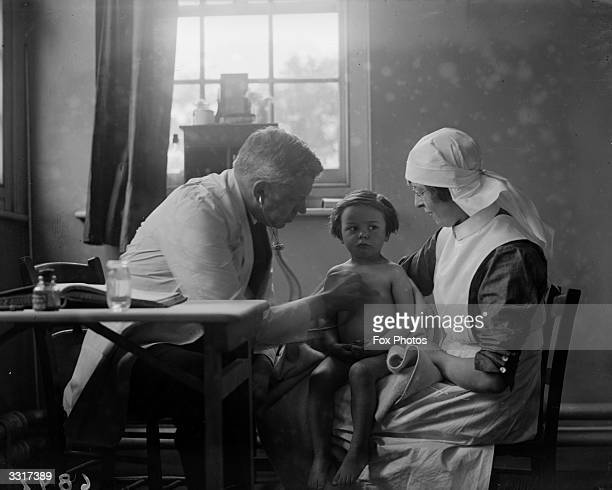 A little girl is reassured by a nurse as a doctor listens to her chest with a stethoscope at the Homeless Children's Aid Adoption Society