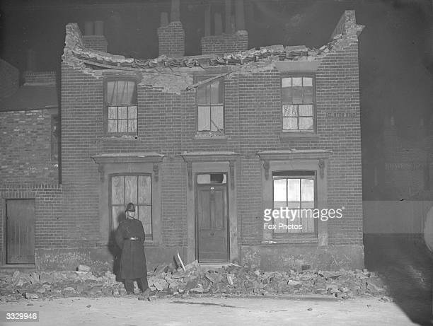 A policeman stands guard in the debris outside a roofless house which has partially collapsed though a light is still on in a window