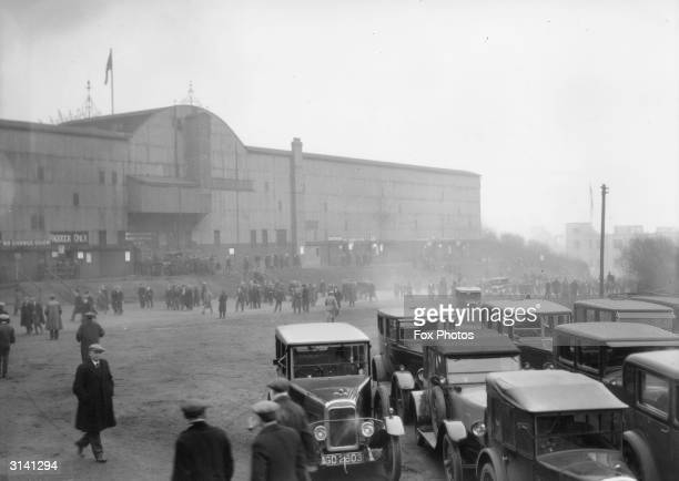 Cars parked outside and pedestrians approaching St James Park, home of Newcastle football club.