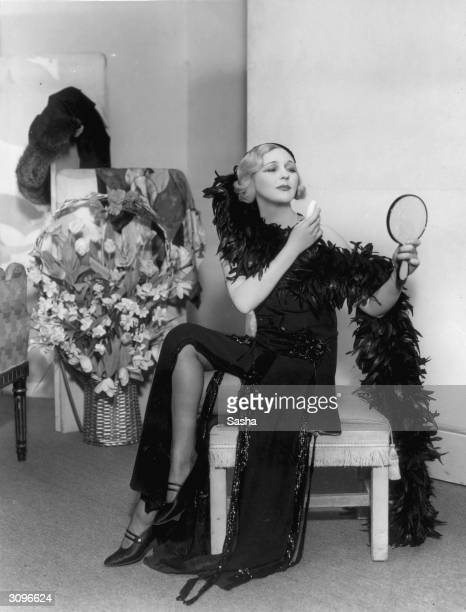 A woman sensationally dressed in a feather boa and beaded gown applies her makeup in a scene from 'Gay Love' at the Lyric Theatre London