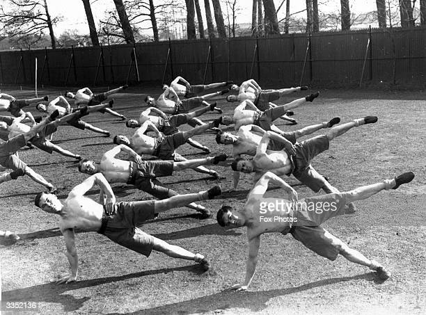 Balancing on one hand and one leg soldiers doing physical training at an army vocational training camp at Aldershot Hampshire