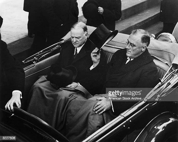 President Roosevelt tips his top hat while sitting in the back of a car with former President Herbert Hoover at the inauguration in Washington D.C.