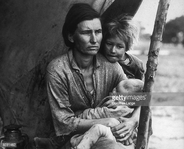 The mother of a migrant family holds a baby while a young girl stands behind her and rests her chin on her shoulder under a leanto Nipomo California