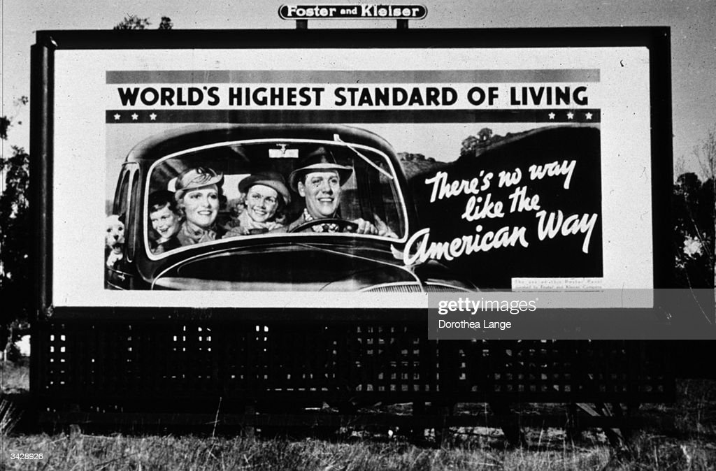 A billboard, sponsored by the National Association of Manufacturers, on Highway 99 in California during the Depression. It reads 'There's no way like the American way' and 'world's highest standard of living'.