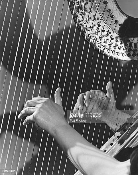 A pair of hands plucking the strings of a harp