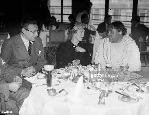 Left to right film director Alexander Korda and film actors Mary Pickford and Charles Laughton together in a restaurant possibly during filming of 'I...