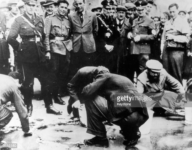 Nazi soldiers and party members watching Jews being forced to scrub the pavements of Vienna