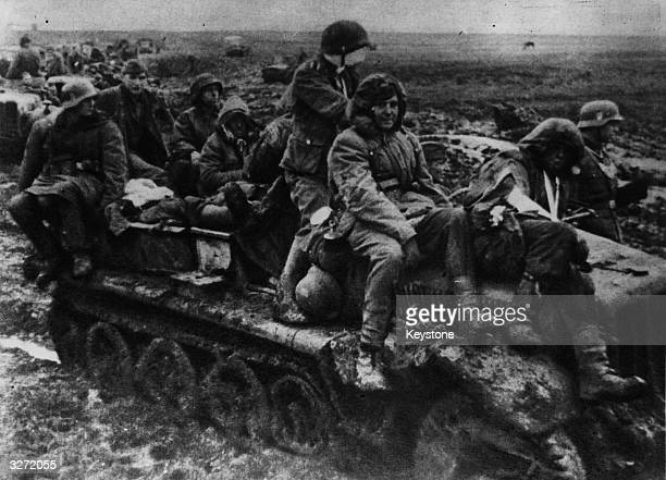 German troops sit on a tank improvising transport to stretcher a wounded comrade on the muddy cold Eastern Front
