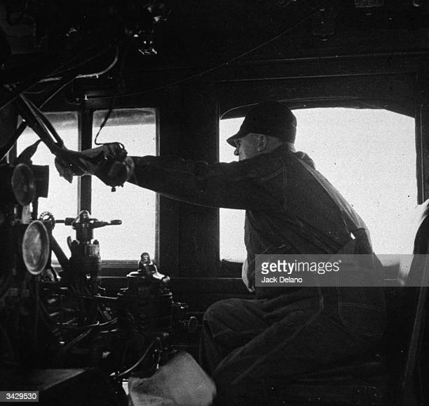B F Hale an engineer in the cab of an engine on the Atchison Topeka and Sante Fe Railroad in Kiowa Kansas