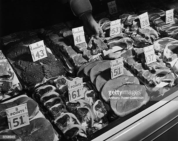 Meat cuts with ceiling prices and point values per pound properly displayed in a butcher's case World War II