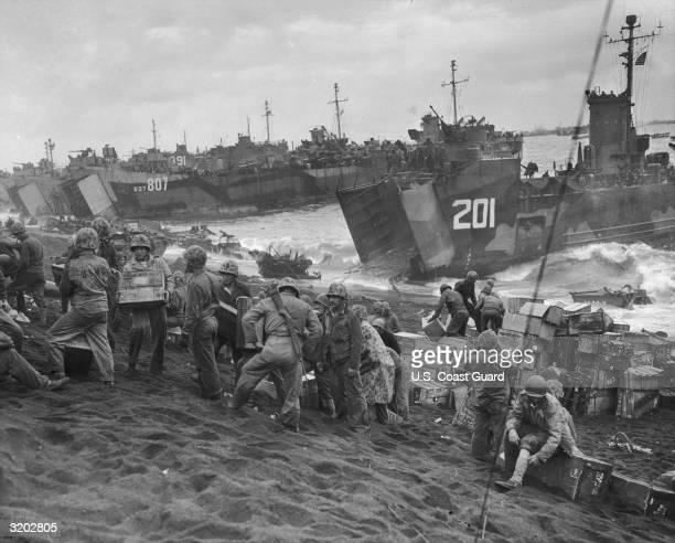 Fulllength image of members of the US Navy and Coast Guard arriving on the shores of Iwo Jima hours after the Marines had succeeded in capturing the...