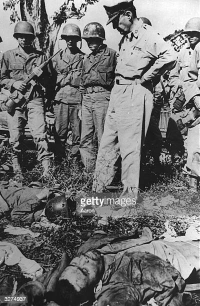 General Douglas MacArthur looks down on dead Japanese soldiers after a fierce battle on Bataan