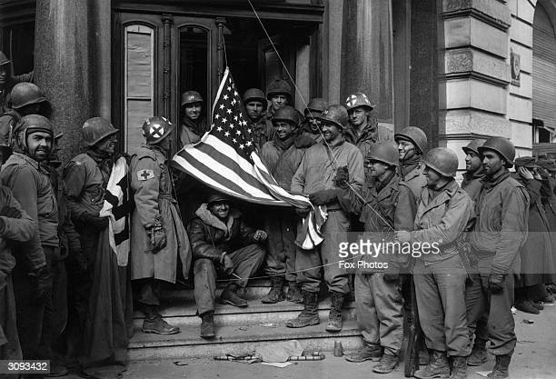 Soldiers of the US Third Army exchange the Nazi swastika in front of the Porta Negre Hotel the Nazi headquarters in Trier for an American flag upon...
