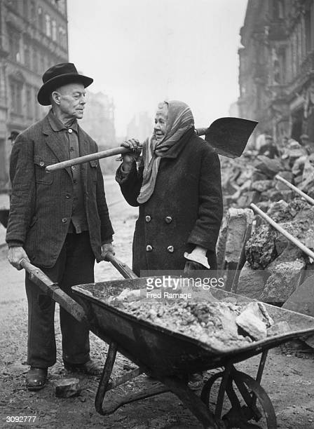 An elderly couple do their best to help clear the debris during the postwar reconstruction of bombdamaged Dresden in Germany