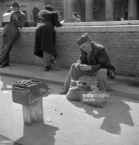 In post war Rome an old soldier roasts chestnuts on the street