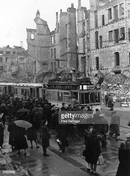 People in Dresden queuing for one of the few trams spared by the bomb damage which devastated the transport system
