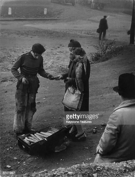 Woman with a fur stole supplements her bread ration with loaves from a black market trader in Milan. Illegal bread costs 350 lire per kilo, a third...