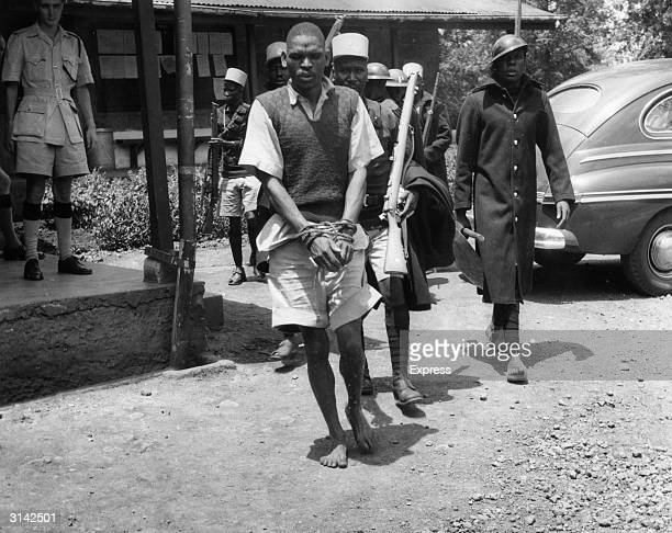 A Mau Mau suspect detained by the police is led away with his hands bound with rope during the Mau Mau revolt in Kenya
