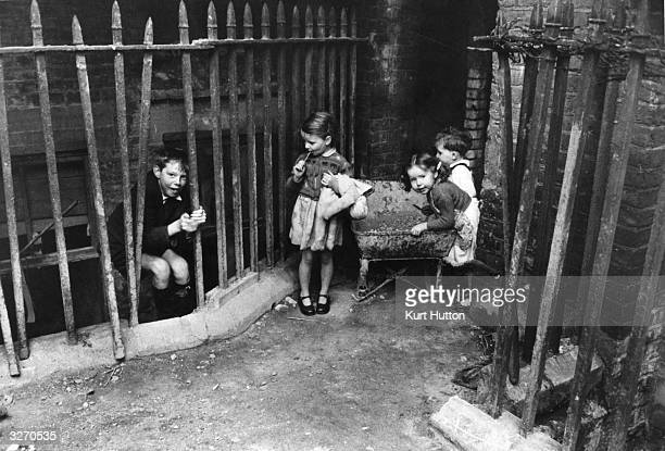 Children from povertystricken families playing at Jubilee Buildings Wapping a slum dwelling in east London Original Publication Picture Post 6845 The...