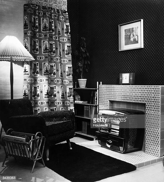 A magazine rack heater lamp armchair and bookcase in a tidy living room with luridly patterned curtains Housewife pub 1955