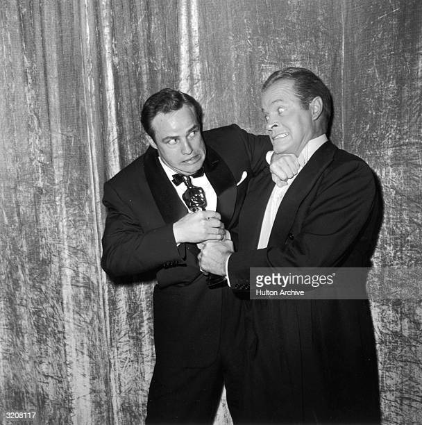 British-born entertainer Bob Hope jokingly tries to wrestle an Oscar statuette away from American actor Marlon Brando, backstage at the Academy...