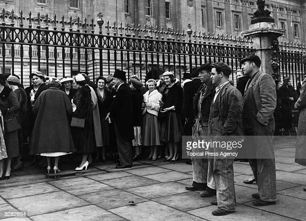 The contrast in dress is evident as workmen study the debutantes waiting to enter Buckingham Palace for the Queen's presentation party