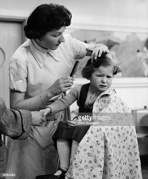 Little girl has to hold her mother's hand while a hairdresser styles her hair.