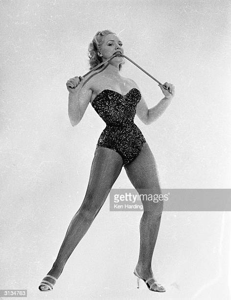 Glamorous strongwoman and model Joan Rhodes of Hampstead north London bends an iron bar with ease using her teeth