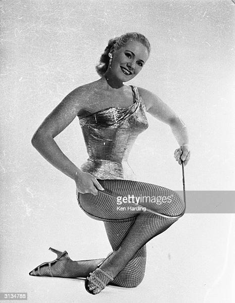 Glamorous strongwoman and model Joan Rhodes of Hampstead north London bends an iron bar with ease