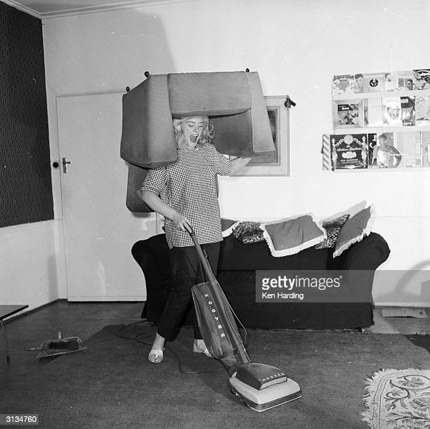Glamorous strongwoman Joan Rhodes exercises her strength whilst hoovering in her flat in Hampstead north London