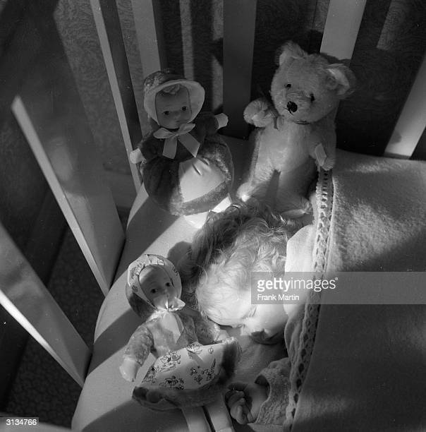 Little Anne sleeps soundly with a selection of British made luminous toys which glow in the dark