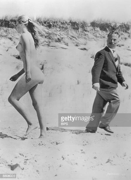 A fullyclothed man turns to stare in disgust at a passing naturist on the beach