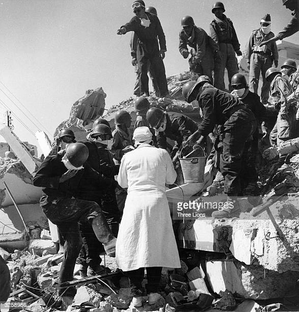 Rescueworkers lift an earthquake victim from rubble in Agadir Morocco while a doctor makes an identification