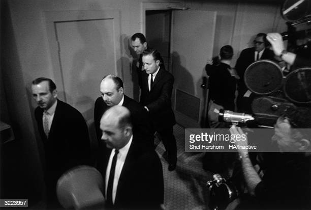 Jack Ruby is escorted by security officials down a corridor of a courthouse during the murder trial of Lee Harvey Oswald Dallas Texas He was...
