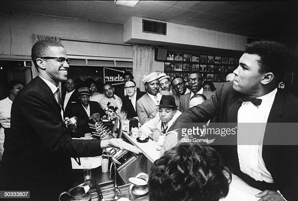Black Muslim leader Malcolm X behind soda fountain with tuxclad Cassius Clay while surrounded by jubilant fans after he beat Sonny Liston for the...