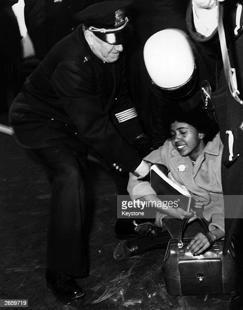 A black woman is arrested by police in front of the White House in demonstrations following the death of Reverend Reep from a beating he received...