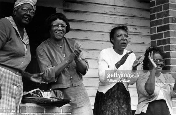 Four black women applauding while watching a civil rights march from Selma, Alabama, to the state capital in Montgomery.