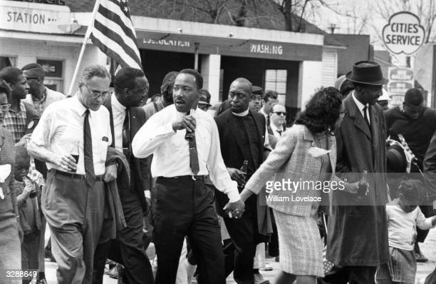 Martin Luther King and his wife Coretta Scott King lead a civil rights march from Selma, Alabama, to the state capital in Montgomery. On the left is...