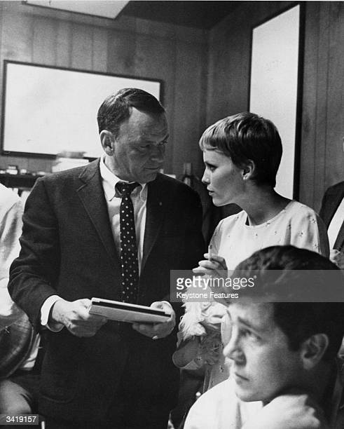 Film actor and popular singer Frank Sinatra chats with his young wife actress Mia Farrow during a break in a recording session at Hollywood's Sunset...