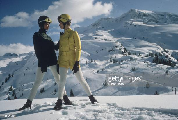 Two women pose on a mountain in the Alps wearing ski helmets coloured jackets and white leggings