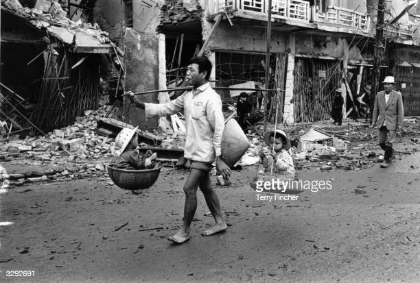 A Vietnam War refugee returns to Hue carrying two children in baskets suspended from his shoulder