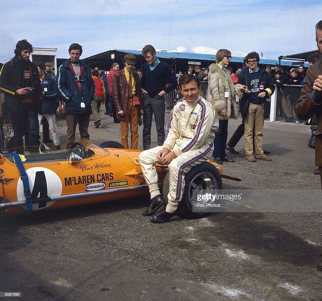 New Zealand motor-racing driver Bruce McLaren (1937 - 1970) sits on the wheel of his McLaren-Ford M14A before the start of the Race of Champions at Brands Hatch in Kent.