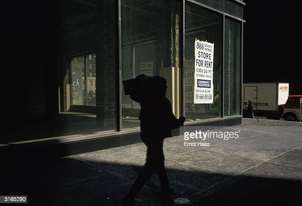 In New York a man carrying a box on his shoulders is silhouetted against a large glassfronted corner store which is for rent