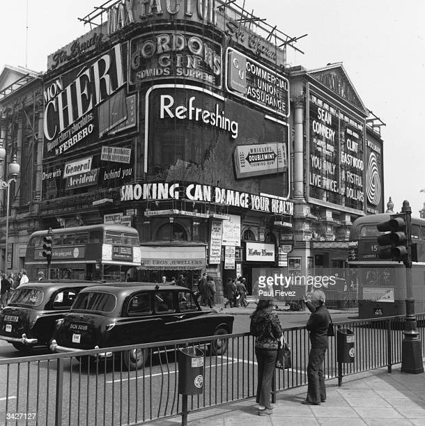 Piccadilly Circus in London with its famed neon advertisements including the British Health Council's new warning 'Smoking Can Damage Your Health'