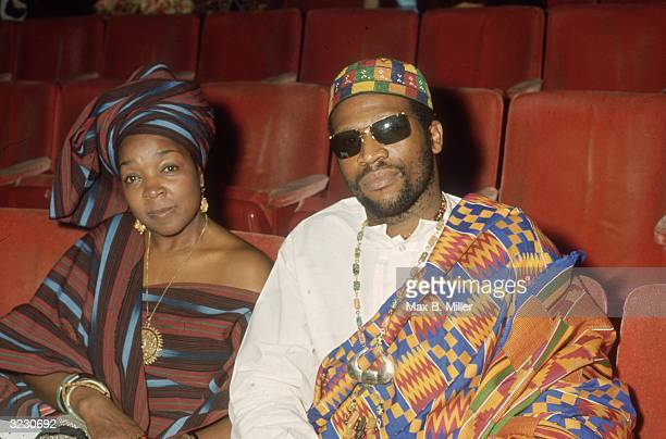 American folk and blues musician Taj Majal sits in his seat beside an unidentified woman at the Academy Awards Los Angeles California They wear kente...