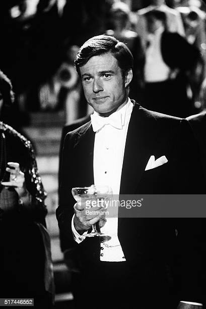 Movie still from 'The Great Gatsby' shows Robert Redford in a tuxedo holding a champagne glass Waistup photo