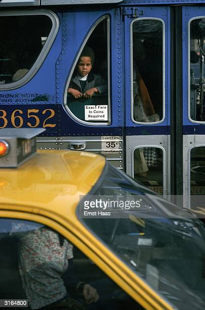 A yellow cab passes a blue bus on a New York street A young girl gazes out of the window of the bus