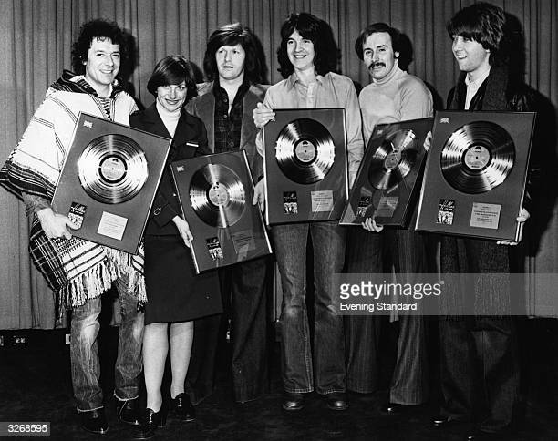 Pop group The Hollies and a friend hold gold disc awards presented to them for record sales From left to right Allan Clarke unknown Bobby Elliot...